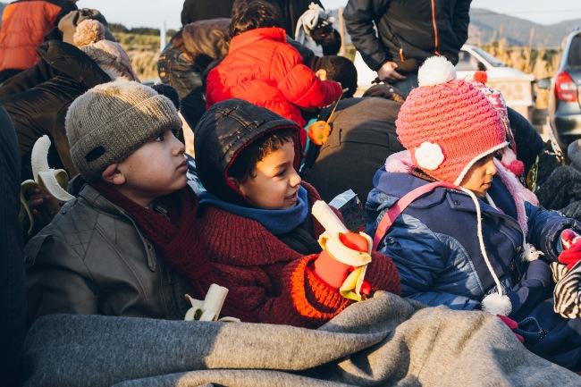 Rannalla syyrialaiset lapset saavat vilttejä, kuivia vaihtovaatteita ja banaaneja vapaaehtoisilta. Kuva: Sami Lensu.